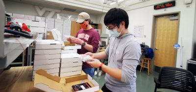 Students Travis Bowman and Henry Zhao help with assembly of take-home lab kits.