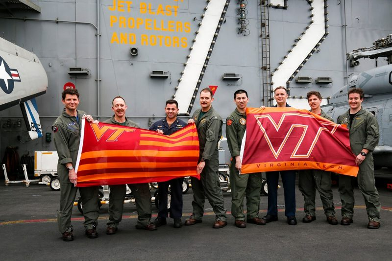 Hokie alumni deployed with the Carrier Strike Group 12 include, from left, Cmdr. Matthew Wright, Cmdr David Dartez, Lt. Cmdr. Anthony LaVopa, Lt. Nick Len, Lt. Tom Clapp, Aerographer's Mate 2nd Class Patrick Nichols, Lt. Joe Haslem, and Lt. Jonathan Bressette.