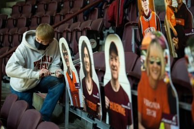 Eric Link, a junior and a member of the American Society of Mechanical Engineers at Virginia Tech, puts the final touches on the moving Hokie cutouts at Cassell Coliseum. Photo by Ryan Young.